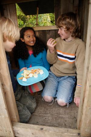 Children having picnic in treehouse