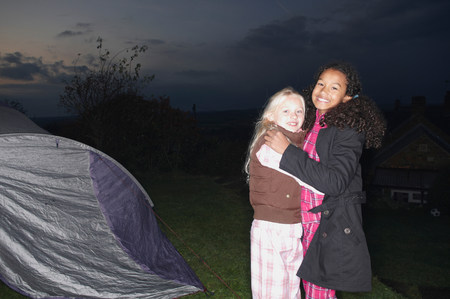 Girls in near tent at dusk
