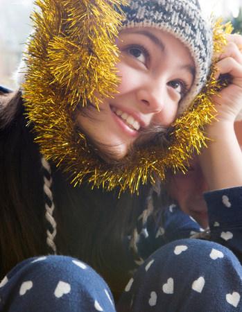 Girl, 14 holding Christmas tinsel Stock Photo
