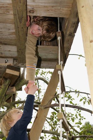 Boy helping friend to treehouse
