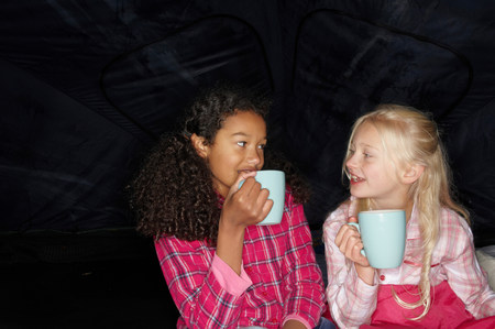 Girls with hot drink in tent