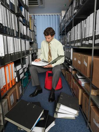 Office worker surrounded by files Reklamní fotografie