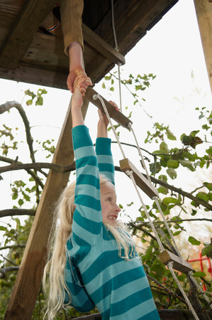 Boy helping girl to treehouse Imagens
