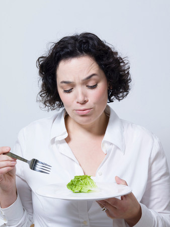 woman looking at a leaf of salad