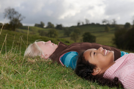 Two girls lying on grass looking at sky