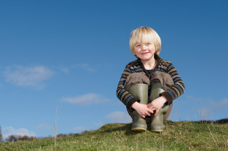 Young boy on hill in countryside Stock Photo