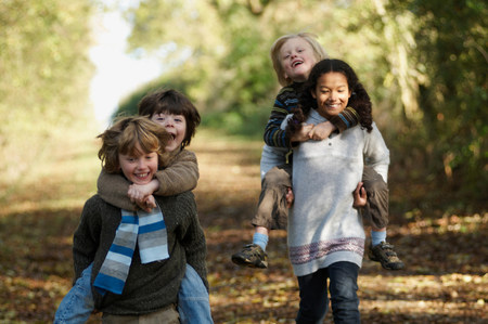 Kids in piggyback races on country lane