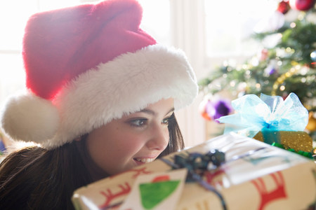 Girl, 14 looking at Christmas present Stock Photo