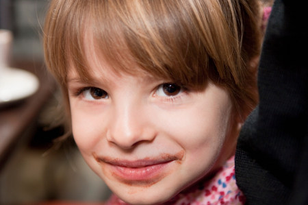 Girl with chocolate around mouth