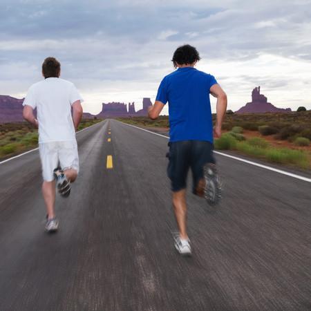 Two men jogging on road in desert
