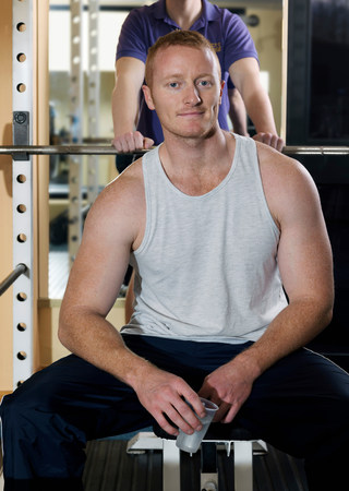 man relaxing with weights at gym