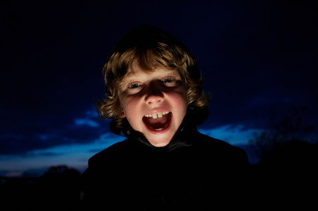 Boy making faces with flashlight