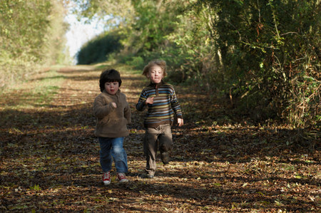 Two boys racing on country lane