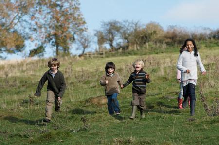 Children running down hill in field 스톡 콘텐츠