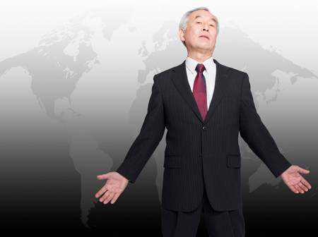 Asian man standing in front of world map