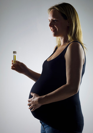 pregnant woman with sample bottle