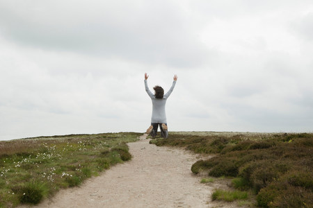 Woman jumping on path in moors 写真素材