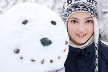Portrait of teenage girl next to snowman
