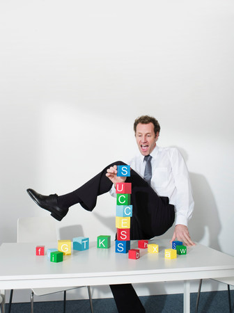 Business man puts last block on tower Reklamní fotografie