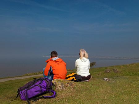 man & woman resting on hike