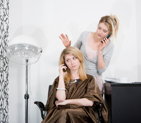 Woman and hair stylist on phones Stock Photo