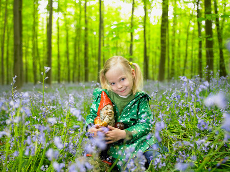 Girl with a garden gnome, in the woods