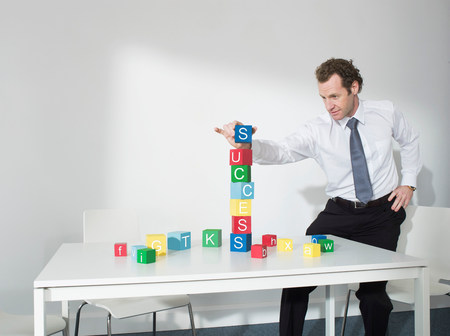 Business man playing with blocks