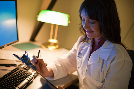Female Doctor working at desk at night