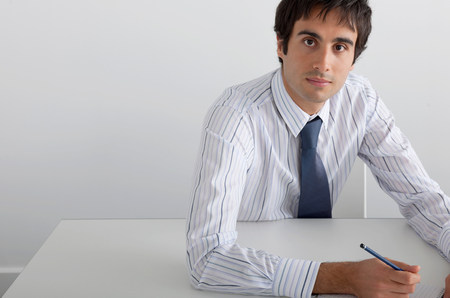Businessman sitting at white table Imagens