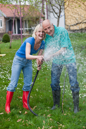 woman and old man playing with hose