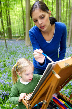 Mother and daughter painting, outdoors Imagens