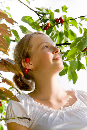 girl picking cherries on tree