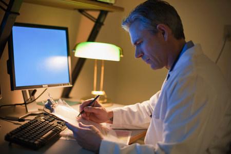 Male Doctor working at desk at night Reklamní fotografie