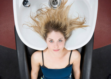 woman at sink at hairdressers Stock Photo