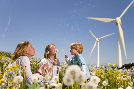 Girl and boy and mother at wind turbines 写真素材