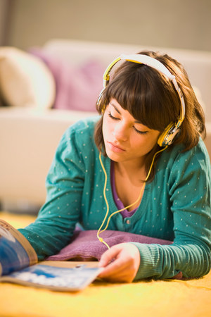 Girl with headphones and magazine Фото со стока