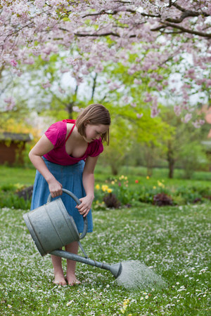 young girl watering grass Stock Photo