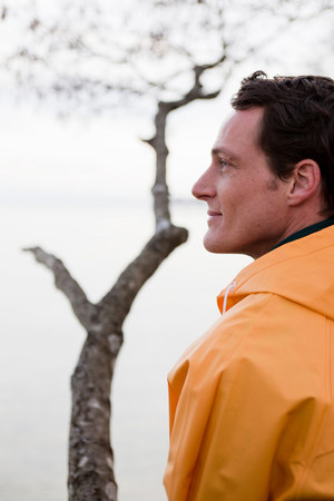 man in raincoat looking on a lake