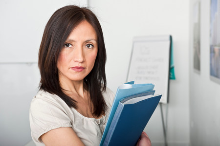 woman looking to camera holding files