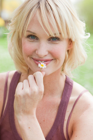 woman with flower smiling at viewer Stock Photo
