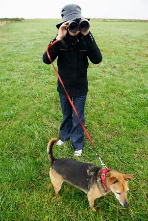 Girl with binoculars, walking the dog
