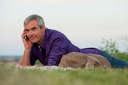 man with dog on the phone in the grass