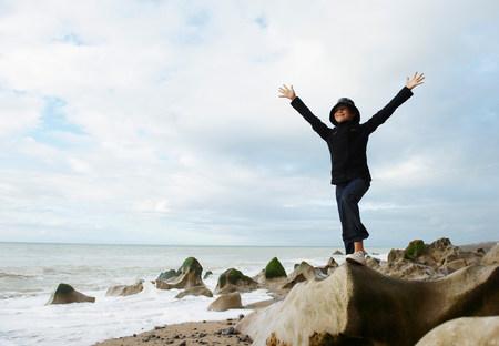 Girl spreading arms towards ocean