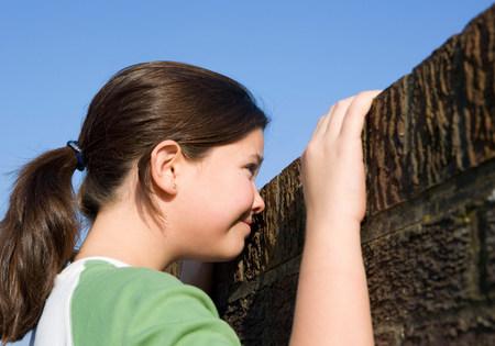 Chica mirando por encima de la pared