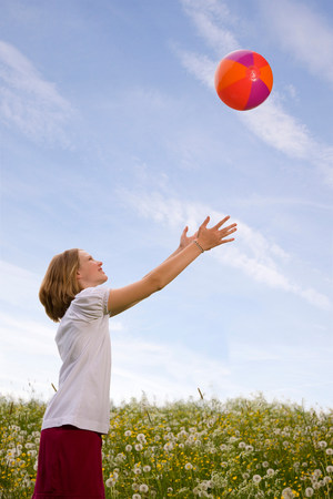 Girl in meadow playing ball