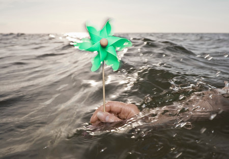 Arm holding windmill towards sea Reklamní fotografie