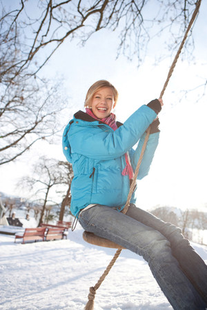 Scandinavian teenage girl on a swing
