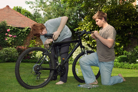 Boys fixing bicycle together Banco de Imagens