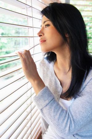 Woman looking through window Stock Photo
