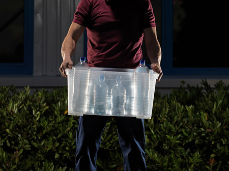 man carrying box of water at night